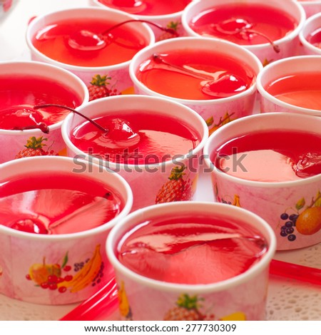 Cherry dessert arranged in paper cups.Focus on middle front cup. - stock photo