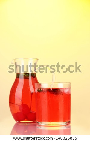 Cherry drink in pitcher and glass on yellow background
