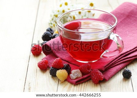 cherry fruit tea in a glass cup and fresh berries - stock photo