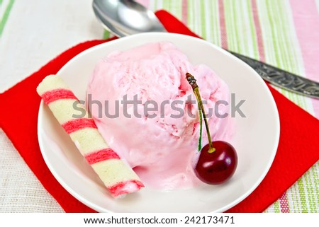 Cherry ice cream in a bowl with wafer rolls on a red paper napkin, spoon on a background of striped linen tablecloths - stock photo