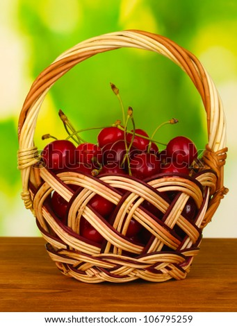cherry in basket on wooden table on green background