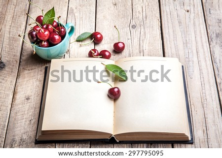 Cherry in the beautiful turquoise cup and old book on a wooden table. Fruit, education - stock photo