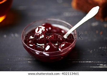 Cherry jam in a glass bowl on a black wooden background. Close view. Shallow depth of field - stock photo