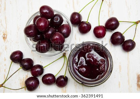 Cherry jam with fresh cherries on a wooden background - stock photo