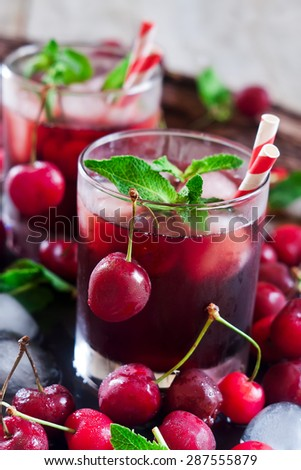 Cherry juice with ice cubes, mint leaves and ripe sweet cherry - stock photo