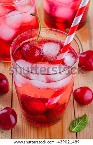 cherry lemonade with ice in glasses on a wooden table wooden table