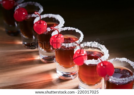 cherry liquor with berry on wooden table - stock photo