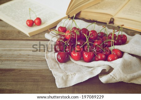 Cherry on a background of old books. Toned vintage - stock photo