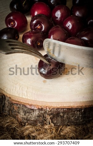 Cherry on a cut tree with old knife and fork