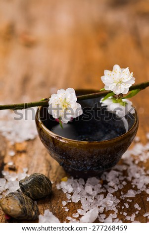 Cherry on bowl and stones ,pile of salt on old wood - stock photo