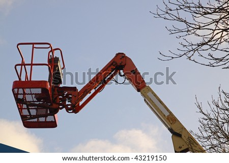Cherry picker aligned with a tree top - stock photo