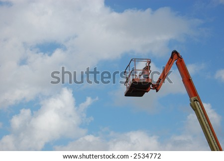 Cherry Picker crane against a blue sky with clouds - stock photo