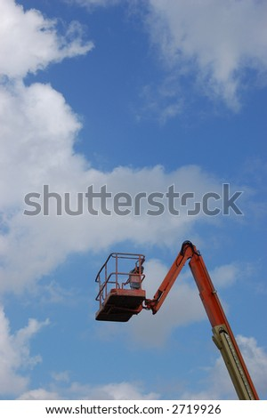 Cherry Picker crane against blue sky with clouds with plenty of copyspace in a vertical format. - stock photo