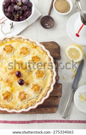 Cherry pie homemade on a white textile background - stock photo