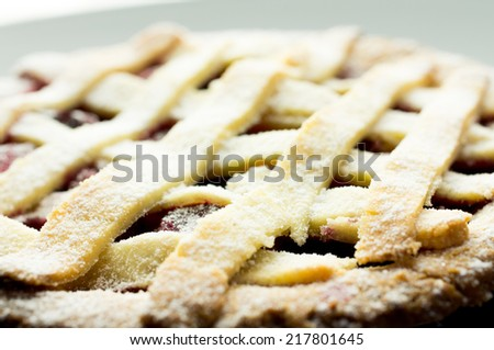 Cherry pie with lattice top on a black plate - stock photo