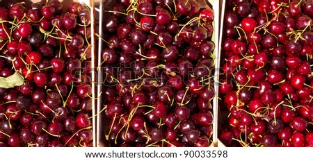 Cherry red fruits in wooden baskets at the market