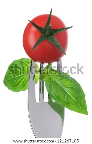 cherry tomato and basil leaves on a fork against a white background - stock photo