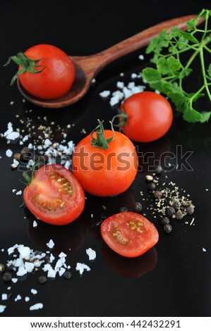 Cherry tomato with salt and black pepper on black background - stock photo