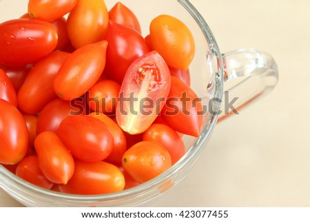 Cherry tomatoes. A handful of cherry tomatoes in glass. - stock photo