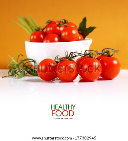 Cherry tomatoes and garlic on white background.