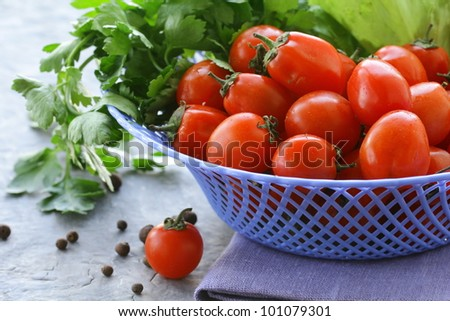 Cherry tomatoes and herbs in a wicker basket - stock photo