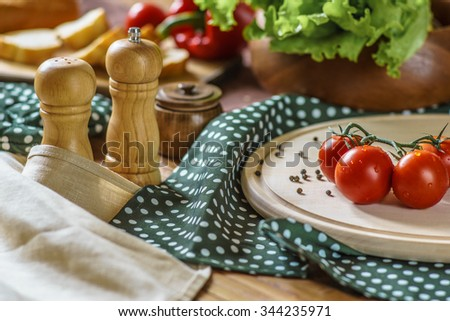 Cherry tomatoes and some kitchen stuff and food - stock photo