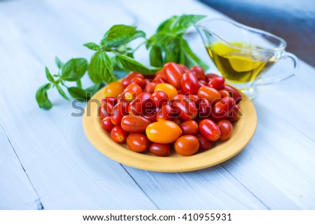 Cherry tomatoes, basil and olive oil on a wooden table. - stock photo
