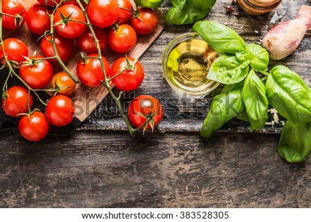 Cherry Tomatoes, basil and olive oil on wooden background, top view. Italian food cooking ingredients. - stock photo