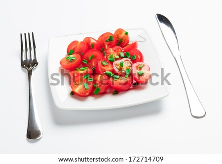 Cherry tomatoes decorated with green onions. On a white square plate.