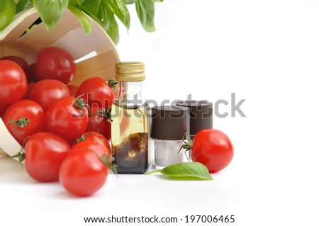cherry tomatoes dumped a basket with little bottles of vinaigrette and salt  - stock photo
