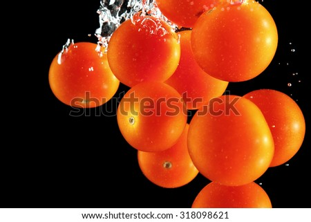 Cherry tomatoes falling into water at black background - stock photo
