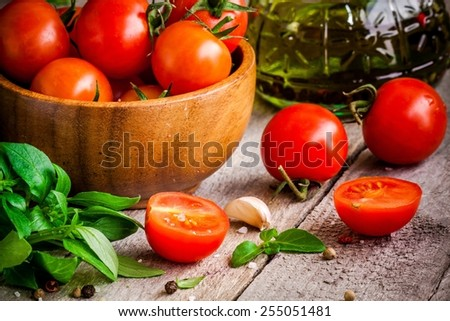cherry tomatoes, fresh organic basil, garlic, olive oil on rustic wooden background - stock photo