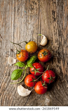 Cherry tomatoes, garlic and fresh basil on vintage wood table - rural still life from above. Harvest from garden. Background layout with free text space. - stock photo