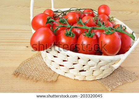 Cherry tomatoes in a basket over wooden background.