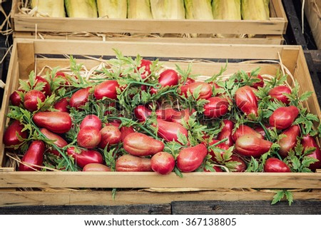 Cherry tomatoes in the wooden box. Vegetables market.