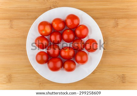 Cherry tomatoes in white glass plate on wooden table, top view - stock photo