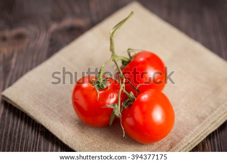 Cherry tomatoes in white metal bowl on a wooden dark background - stock photo