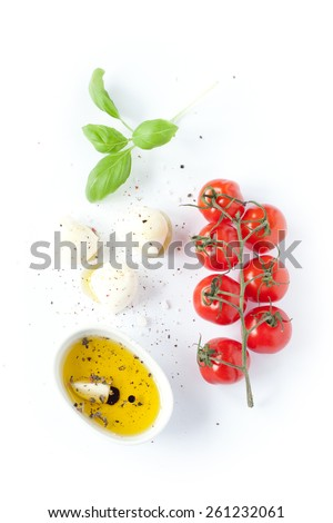 Cherry tomatoes, mozzarella cheese, basil and olive oil on white background from above. Italian caprese salad recipe ingredients. - stock photo