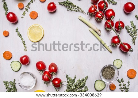 cherry tomatoes on a branch with Sliced cucumber lemon carrots various herbs seasoning salt lined frame place for text on wooden rustic background top view close up - stock photo