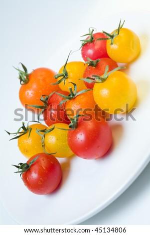 cherry tomatoes on a white plate (diagonal) - stock photo