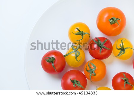 cherry tomatoes on a white plate from above - stock photo