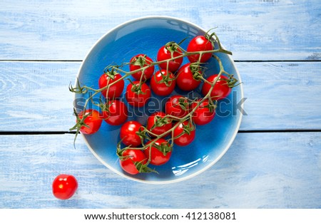 cherry tomatoes on  blue plate - stock photo