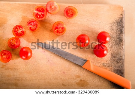 Cherry tomatoes on cutting board with knife (top view)