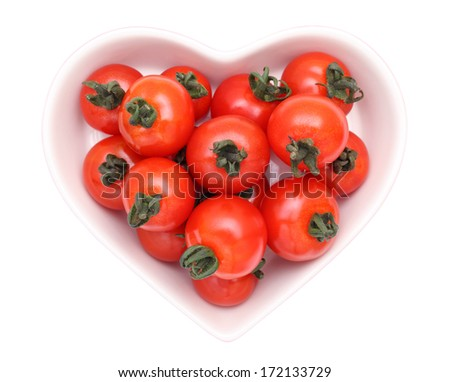 cherry tomatoes on heart-shaped plate, isolated on white background   - stock photo