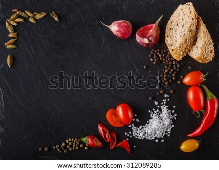 cherry tomatoes on slate with sliced bread, pepper, cardamom and salt. Place to inscription - stock photo