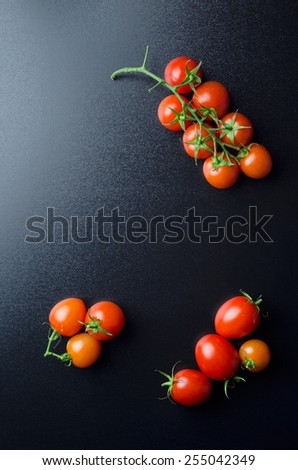 Cherry tomatoes over black board, above view with copy space - stock photo