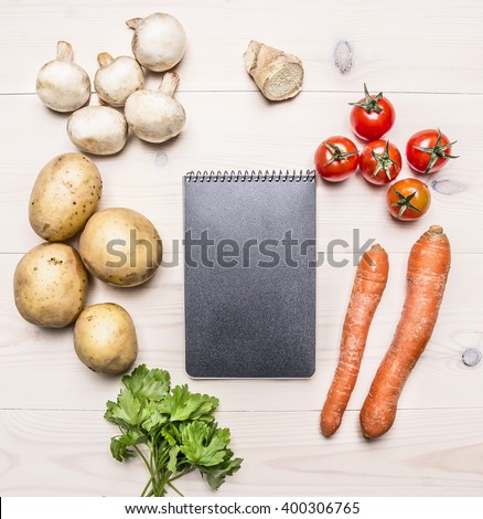 cherry tomatoes, potatoes, carrots, parsley and mushrooms laid out around a notebook place for text,frame on wooden rustic background top view - stock photo