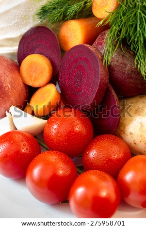 Cherry tomatoes, sliced rings of carrots and beets, potatoes, garlic, onion, dill. Vegetables. Close-up. Vertical shot. - stock photo