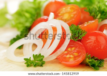 Cherry tomatoes with onion and lettuce on wooden board - stock photo