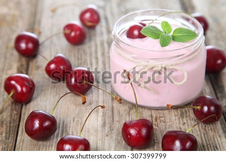 Cherry yogurt and ripe cherry on a wooden table. Summer dessert. - stock photo